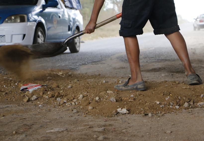 Se autoemplea tapando baches de obras en mal estado en Oaxaca